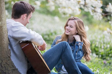 Man playing guitar for girlfriend outdoors Stock Photo - Premium Royalty-Free, Code: 6113-07160630