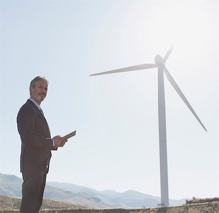 Businessman admiring wind turbine in rural landscape Foto de stock - Royalty Free Premium, Número: 6113-07160881
