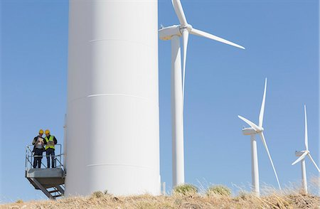 Workers talking on wind turbine in rural landscape Stock Photo - Premium Royalty-Free, Code: 6113-07160884
