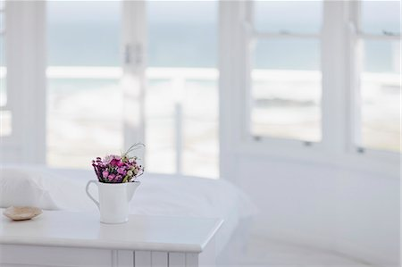 Vase of flowers on desk in bedroom overlooking ocean Stock Photo - Premium Royalty-Free, Code: 6113-07160825