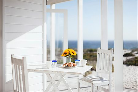 Vase of flowers, coffee and pastries on patio table overlooking ocean Stock Photo - Premium Royalty-Free, Code: 6113-07160835