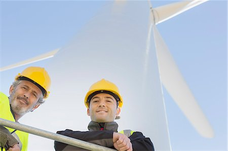 Workers standing on wind turbine in rural landscape Stock Photo - Premium Royalty-Free, Code: 6113-07160943