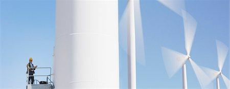 Worker standing on wind turbine in rural landscape Stock Photo - Premium Royalty-Free, Code: 6113-07160941