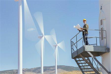 Worker standing on wind turbine in rural landscape Stock Photo - Premium Royalty-Free, Code: 6113-07160942