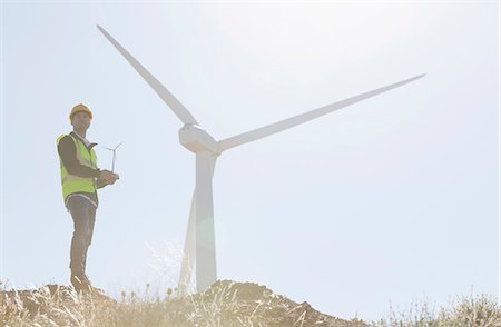 Worker standing by wind turbine in rural landscape Stock Photo - Premium Royalty-Free, Code: 6113-07160947