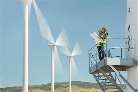 Workers standing on wind turbine in rural landscape Stock Photo - Premium Royalty-Free, Code: 6113-07160944
