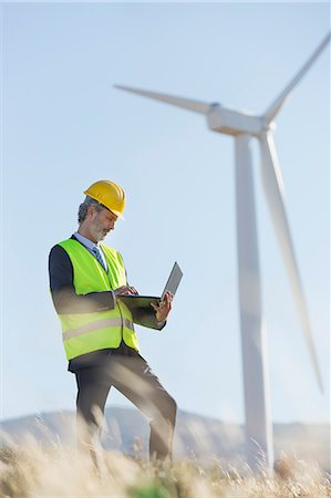 Worker using laptop by wind turbine in rural landscape Stock Photo - Premium Royalty-Free, Code: 6113-07160945