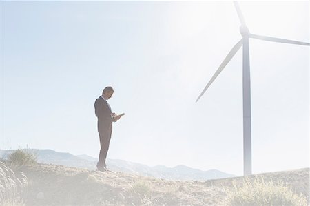 Businessman using laptop by wind turbine in rural landscape Stock Photo - Premium Royalty-Free, Code: 6113-07160949