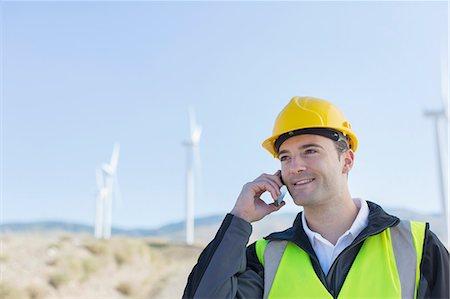 Worker using walkie talkie in rural landscape Stock Photo - Premium Royalty-Free, Code: 6113-07160953