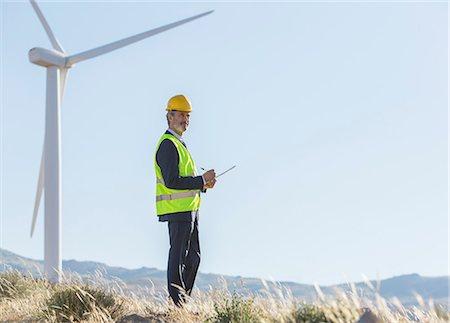 Businessman examining wind turbines in rural landscape Stock Photo - Premium Royalty-Free, Code: 6113-07160957