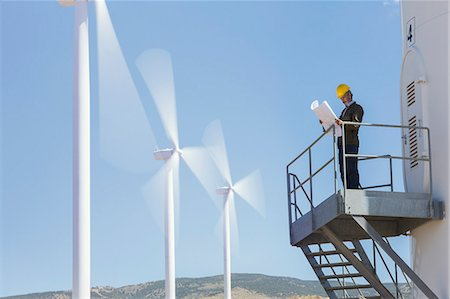Businessman examining blueprints by wind turbines in rural landscape Stock Photo - Premium Royalty-Free, Code: 6113-07160966