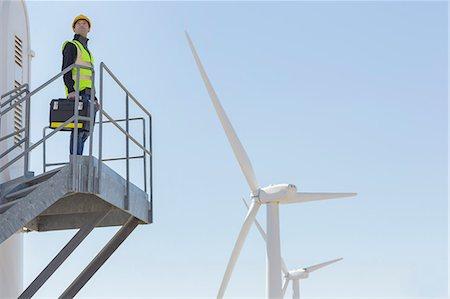 Worker standing on wind turbine in rural landscape Stock Photo - Premium Royalty-Free, Code: 6113-07160968