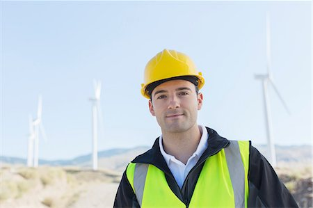 Worker standing by wind turbines in rural landscape Stock Photo - Premium Royalty-Free, Code: 6113-07160904