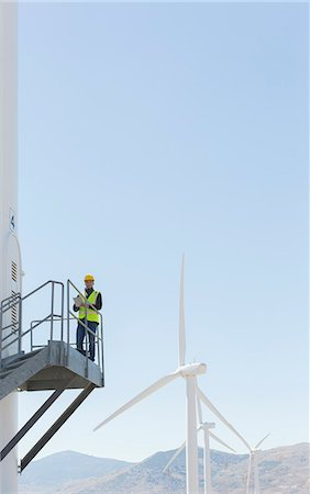 Worker standing on wind turbine in rural landscape Stock Photo - Premium Royalty-Free, Code: 6113-07160905