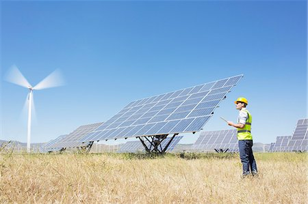solar power - Worker examining solar panels in rural landscape Stock Photo - Premium Royalty-Free, Code: 6113-07160913