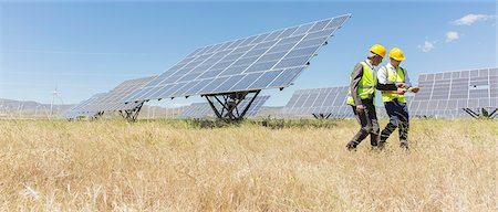 Workers walking by solar panels in rural landscape Stock Photo - Premium Royalty-Free, Code: 6113-07160911