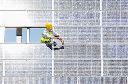 solar power - Worker examining solar panel in rural landscape Stock Photo - Premium Royalty-Free, Code: 6113-07160917