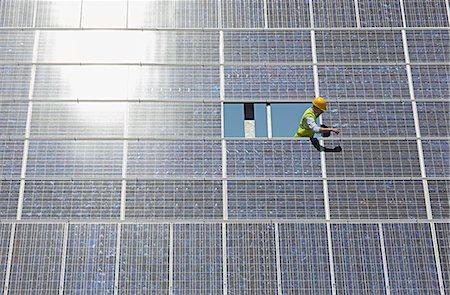 solar power - Worker examining solar panel in rural landscape Stock Photo - Premium Royalty-Free, Code: 6113-07160915