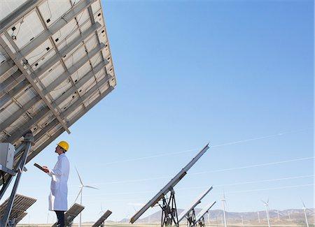 Scientist examining solar panel in rural landscape Stock Photo - Premium Royalty-Free, Code: 6113-07160924
