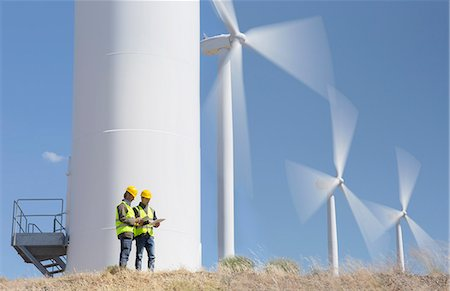 Workers talking by wind turbines in rural landscape Stock Photo - Premium Royalty-Free, Code: 6113-07160928