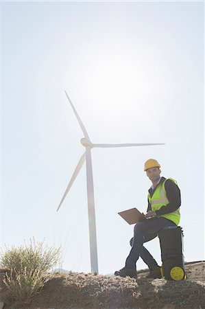 Worker using laptop by wind turbine in rural landscape Stock Photo - Premium Royalty-Free, Code: 6113-07160933