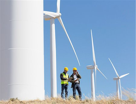 Workers talking by wind turbines in rural landscape Stock Photo - Premium Royalty-Free, Code: 6113-07160931