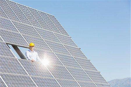 solar power - Worker examining solar panel in rural landscape Stock Photo - Premium Royalty-Free, Code: 6113-07160934