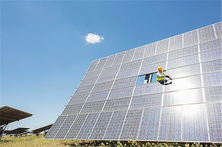 solar power - Worker examining solar panel in rural landscape Stock Photo - Premium Royalty-Free, Code: 6113-07160938