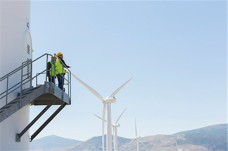 Workers standing on wind turbine in rural landscape Stock Photo - Premium Royalty-Free, Code: 6113-07160939