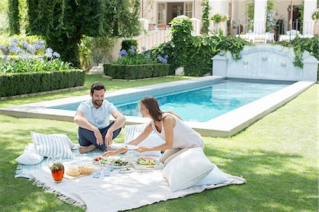 rich lifestyle - Couple enjoying picnic by pool Stock Photo - Premium Royalty-Free, Code: 6113-07241959