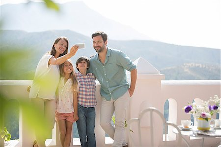 preteen family - Family taking self-portrait on sunny balcony Stock Photo - Premium Royalty-Free, Code: 6113-07241961