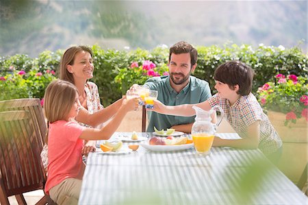 Family toasting orange juice glasses at table in garden Stock Photo - Premium Royalty-Free, Code: 6113-07241965