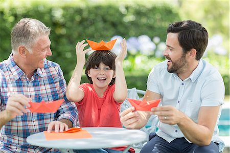 funny pose - Multi-generation men making origami hats outdoors Stock Photo - Premium Royalty-Free, Code: 6113-07241993