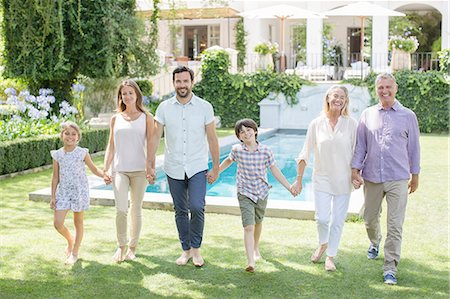 Multi-generation family holding hands and walking in backyard Stock Photo - Premium Royalty-Free, Code: 6113-07242063