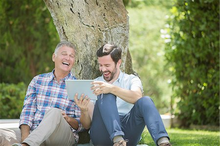 Father and son using digital tablet outdoors Stock Photo - Premium Royalty-Free, Code: 6113-07242061