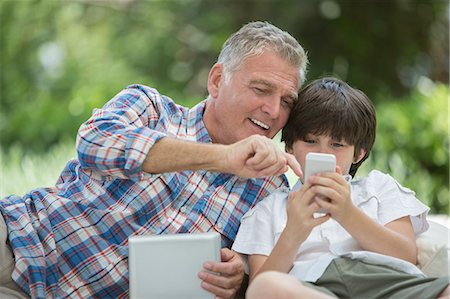 Grandfather and grandson using digital tablet and cell phone Stock Photo - Premium Royalty-Free, Code: 6113-07242001