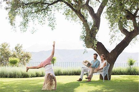 Couple watching daughter do cartwheel outdoors Stock Photo - Premium Royalty-Free, Code: 6113-07242014