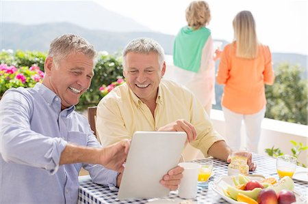 Senior men using digital tablet at patio table Stock Photo - Premium Royalty-Free, Code: 6113-07242021