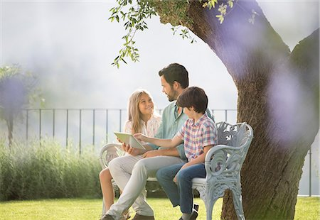 Father and children using digital tablet on bench in park Stock Photo - Premium Royalty-Free, Code: 6113-07242033