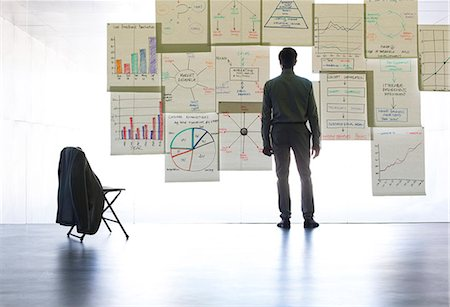 Businessman looking at graphs and charts on glass wall in office Stock Photo - Premium Royalty-Free, Code: 6113-07242143