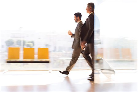 Businessmen walking in airport corridor Stock Photo - Premium Royalty-Free, Code: 6113-07242147