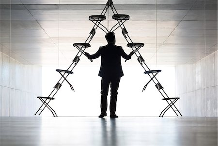 Businessman arranging office chair installation art Stock Photo - Premium Royalty-Free, Code: 6113-07242159