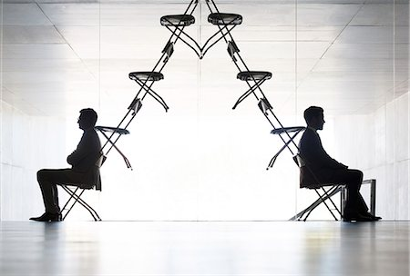 Businessmen sitting at opposite ends of office chair installation art Stock Photo - Premium Royalty-Free, Code: 6113-07242170