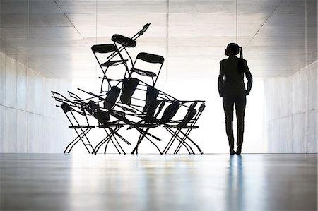 Businesswoman examining office chair installation art Stock Photo - Premium Royalty-Free, Code: 6113-07242190