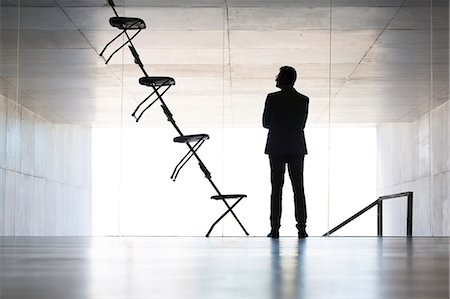 Businessman examining office chair installation art Stock Photo - Premium Royalty-Free, Code: 6113-07242194