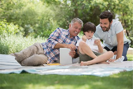 Multi-generation men with cell phone on blanket in grass Stock Photo - Premium Royalty-Free, Code: 6113-07242103