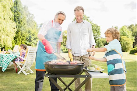 Men grilling meat on barbecue in backyard Stock Photo - Premium Royalty-Free, Code: 6113-07242299