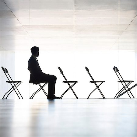Silhouette of businessman sitting in office Stock Photo - Premium Royalty-Free, Code: 6113-07242202