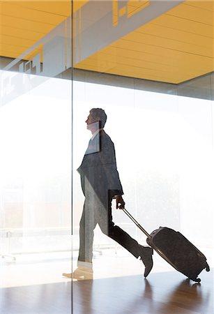 Businessman pulling suitcase in airport corridor Stock Photo - Premium Royalty-Free, Code: 6113-07242224