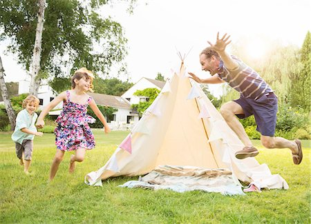 family  fun  outside - Father chasing children around teepee in backyard Stock Photo - Premium Royalty-Free, Code: 6113-07242341